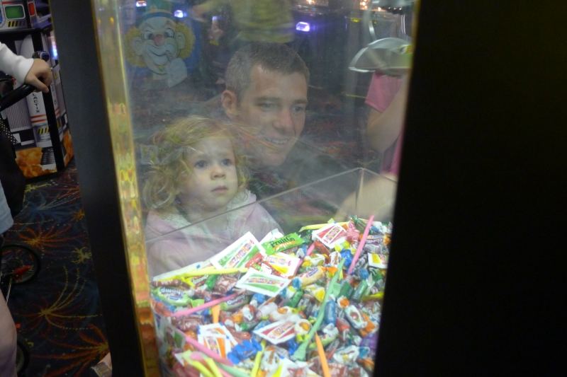 Ava and Cory playing a candy crane game at Seaside