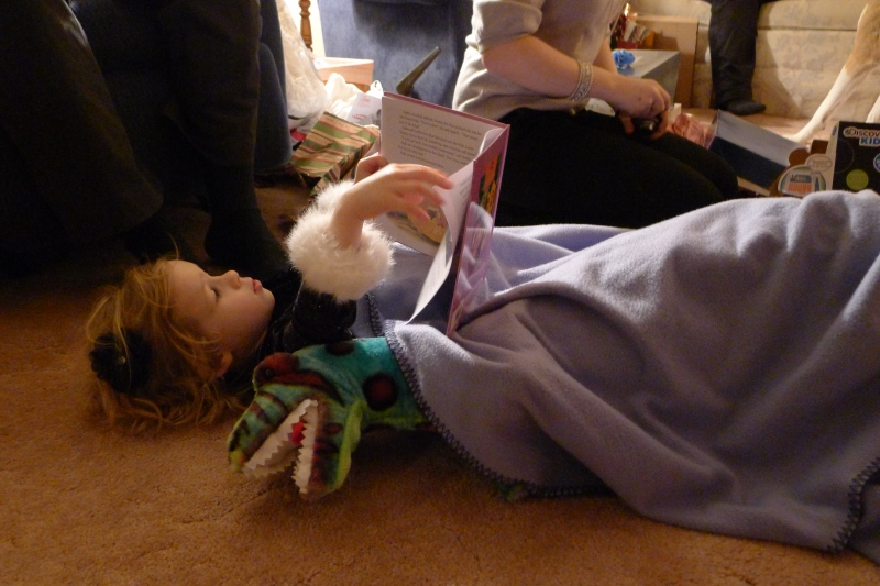 """Ava reading to her 3-foot-tall """"sharptooth"""" - our Christmas gift to her"""