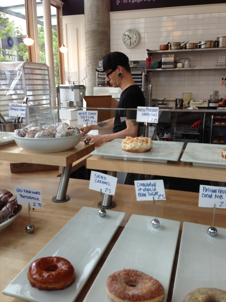 The hipster employee prepares and boxes customers' donuts